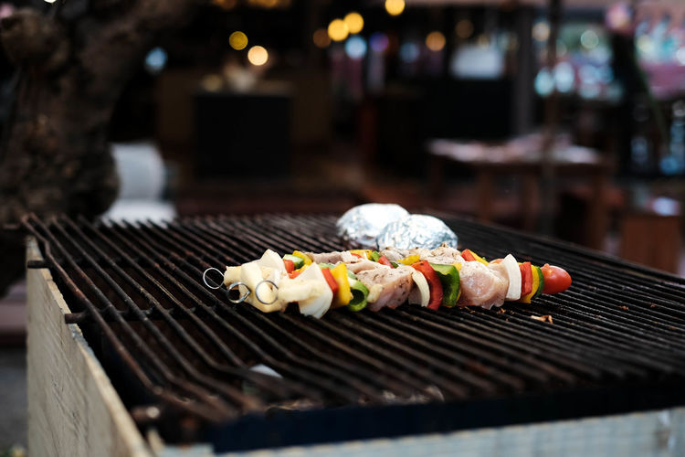 Close-up of meat and vegetables being grilled on barbecue during pool party