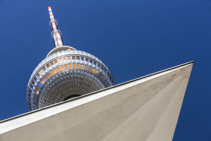 Low Angle View Of Built Structure By Fernsehturm Against Clear Blue Sky