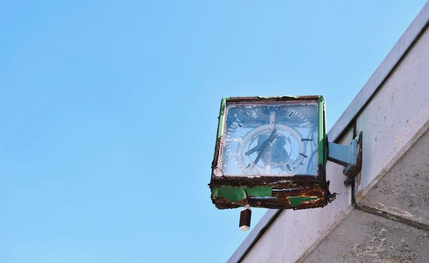 Low angle view of broken clock against clear blue sky