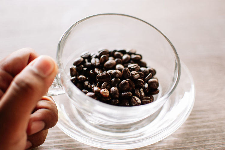 Human Hand Hand Human Body Part One Person Food And Drink Holding Body Part Indoors  Close-up Focus On Foreground Unrecognizable Person Coffee Real People Table Food Coffee - Drink Roasted Coffee Bean Freshness Glass - Material Finger Glass Breakfast
