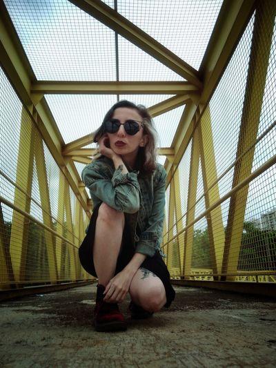 Portrait of woman wearing sunglasses while crouching on footbridge