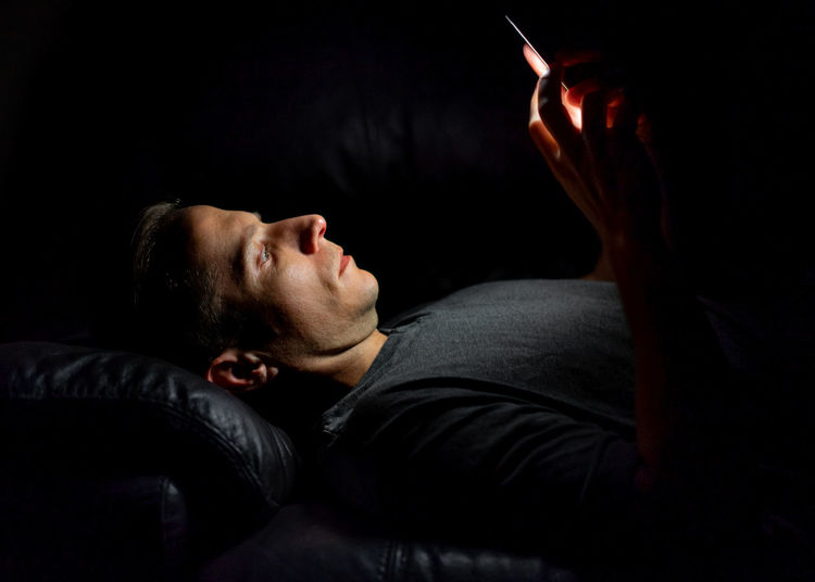 Man using smart phone while lying on bed in darkroom