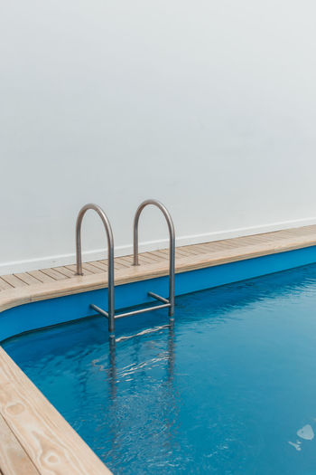 Swimming pool by wall against sky