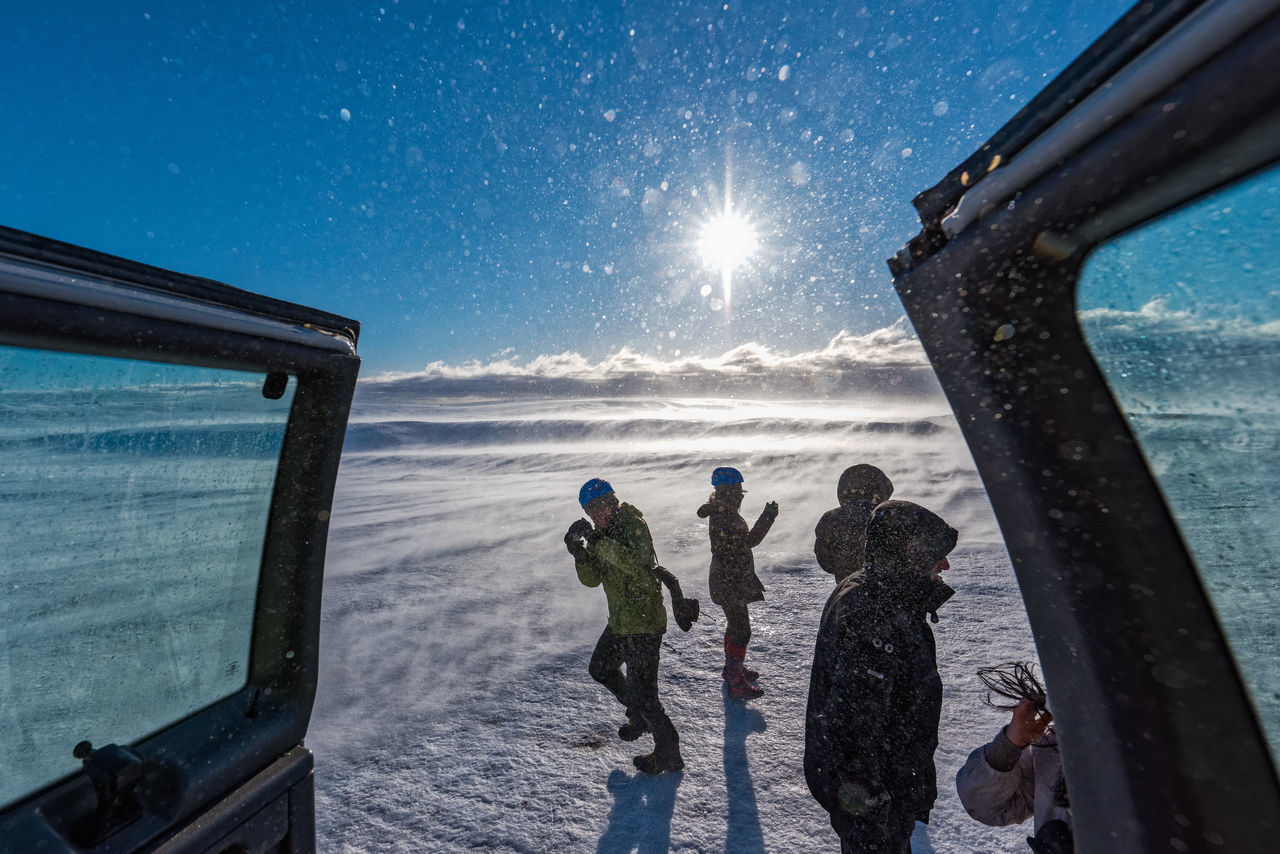 People on field during snowfall against sky