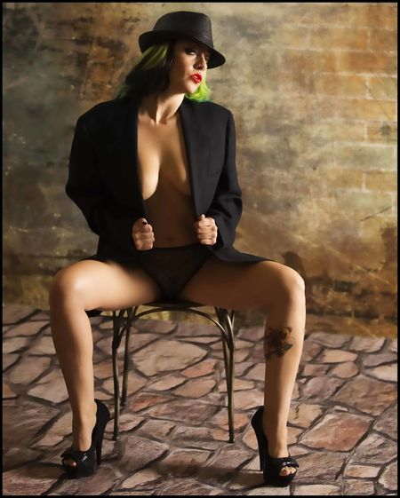Full Length Of Sensuous Woman Sitting On Chair