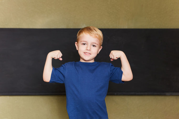 Portrait of cute boy flexing muscles standing against wall