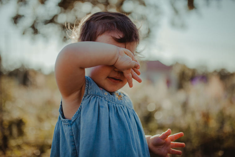 Baby girl covering face while standing outdoors