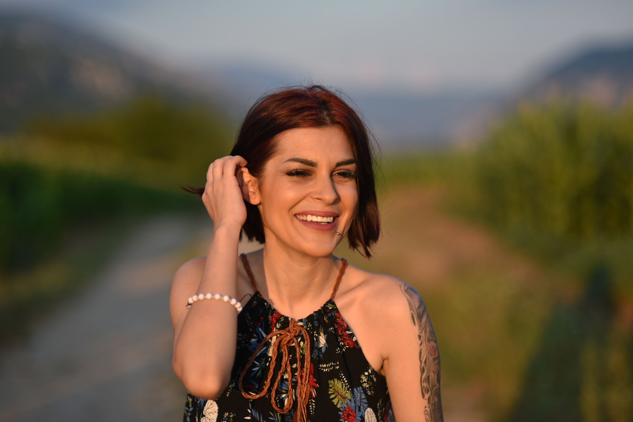 adult, women, smiling, one person, portrait, happiness, emotion, female, nature, portrait photography, human face, person, cheerful, smile, landscape, teeth, dress, lifestyles, photo shoot, young adult, clothing, hairstyle, land, jewelry, beauty in nature, rural scene, brown hair, looking at camera, front view, outdoors, environment, fashion accessory, enjoyment, travel, fashion, waist up, sky, necklace, positive emotion, leisure activity, summer, standing, focus on foreground, copy space, arts culture and entertainment, relaxation, looking, headshot, vacation, trip