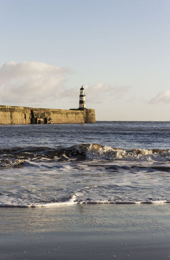 Waves lap the shore at Seaham, Uk with pier and lighthouse Architecture Beach Beauty In Nature Building Exterior Built Structure Day Guidance Horizon Over Water Lighthouse Nature No People Outdoors Scenics Sea Seaham Sky Uk Water Wave
