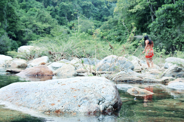 Woman sitting on rock by river in forest