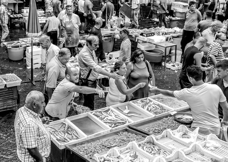 people buying fish at the market in Catania, Sicily, Italy Market Stall For Sale Buying Food And Drink Sale Group Of People Black And White Streetphotography Street Photography Catania Fish Market Sicily Showing Crowd