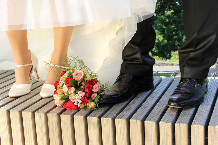 Low Section Of Wedding Couple Standing Outdoors