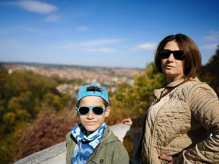 Portrait of smiling boy with mother wearing sunglasses against sky