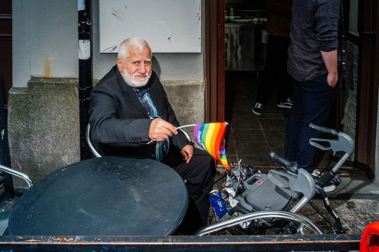 SMILING MAN HOLDING CAMERA WHILE SITTING AT BUS