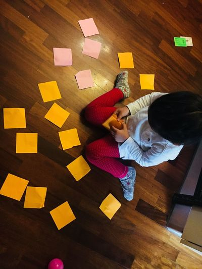 Directly above shot of girl sitting by adhesive notes on hardwood floor