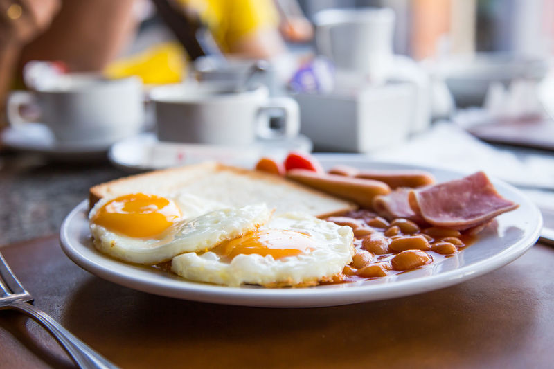 Close-up of english breakfast served in plate on table at restaurant
