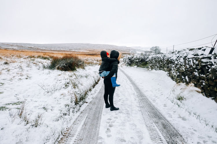 Full length of mother piggybacking son while standing on snow covered road during winter
