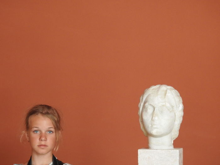 Portrait of girl standing by statue against brown background