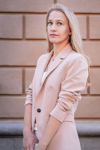 Portrait of a successful business woman with long hair, blonde. in an expensive suit, brick wall