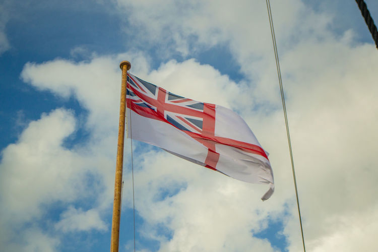 Low angle view of white ensign flag against sky