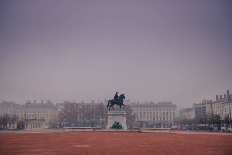 Statue and bellecour square in city against clear sky at the morning