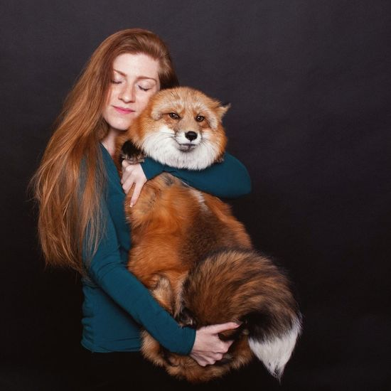 Woman with dog against black background