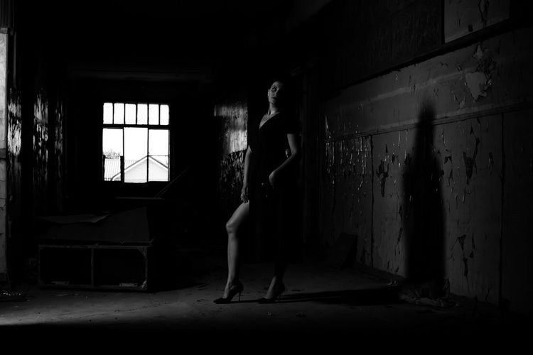 Side view of woman standing in abandoned room