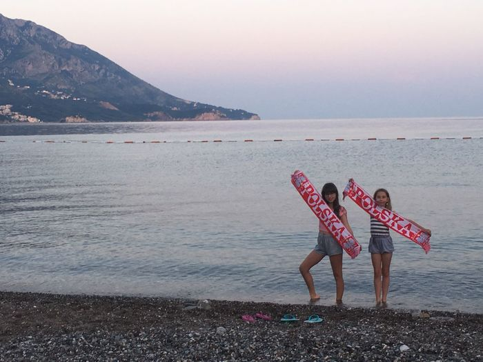 Girls holding fabric with text at beach against sky