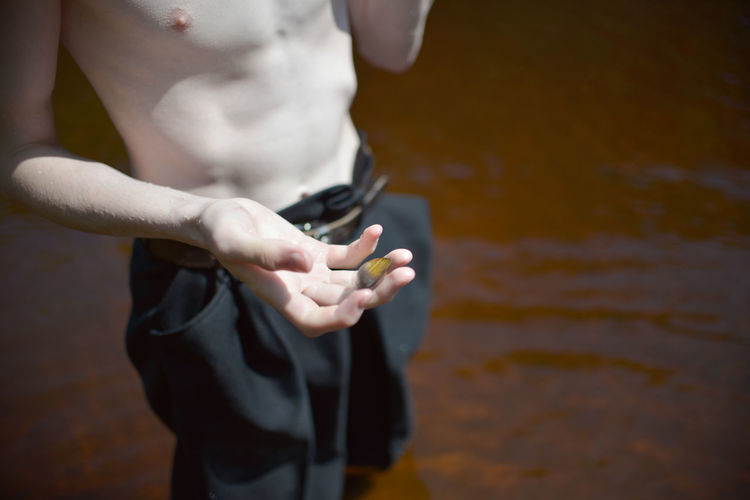 Midsection of man holding while standing by water
