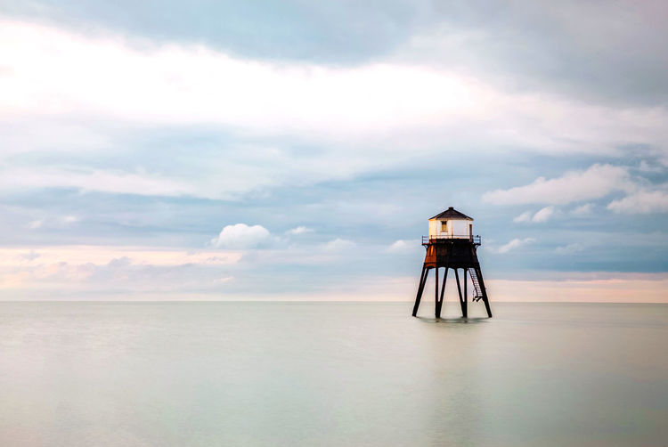 Lifeguard tower by sea against sky
