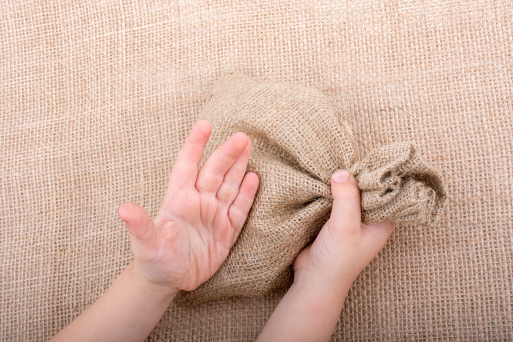 High angle view of child holding burlap sack on table