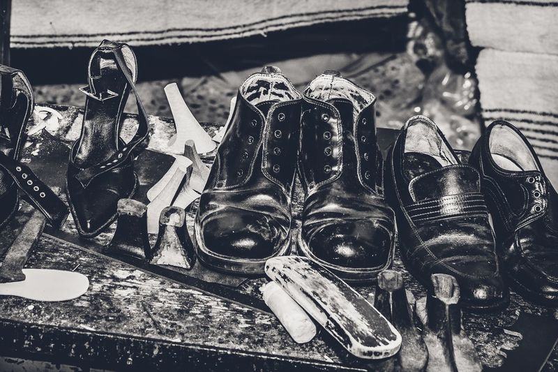 High Angle View Of Shoes With Tools On Table At Workshop