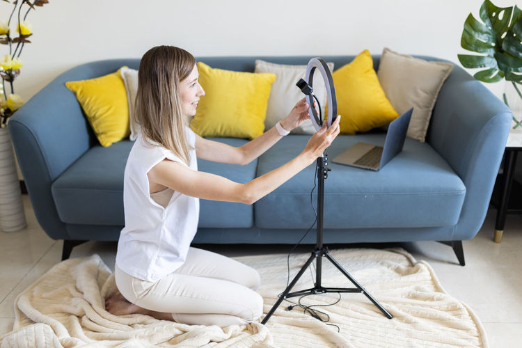 Young woman making photo or video content for social media with smartphone and light of ring lamp.