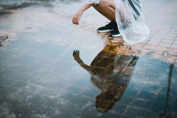 Low section of woman crouching by puddle