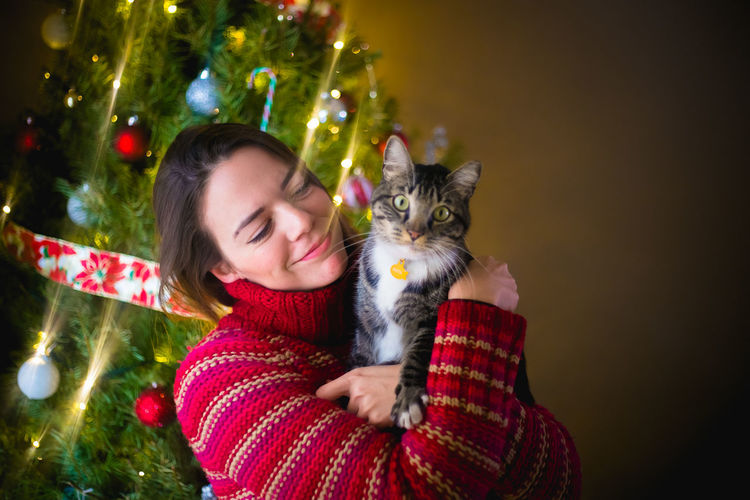 Portrait of woman with cat on christmas tree