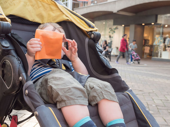 Close-up of baby boy holding envelope while sitting in stroller