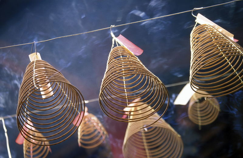 Low Angle View Of Spiral Incense Sticks In Temple