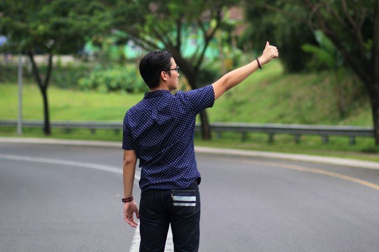 Man showing thumbs up while standing on road