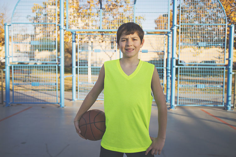 Boy Playing Basketball On Court
