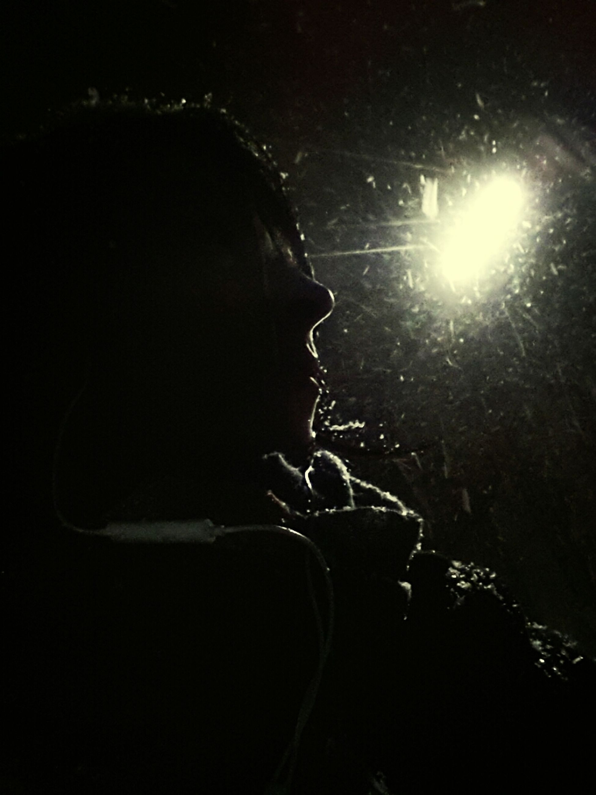 lifestyles, leisure activity, night, men, close-up, headshot, holding, dark, person, light - natural phenomenon, lens flare, unrecognizable person, sunlight, black background, side view, young adult