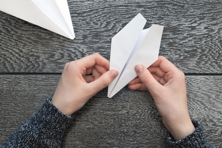 Cropped hands of woman making paper airplane on wooden table