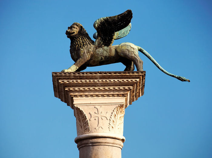 Statue of winged lion on column against clear blue sky at st mark square