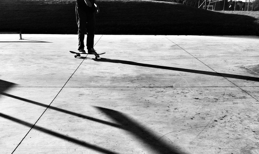 Low section of man skateboarding on walkway during sunny day