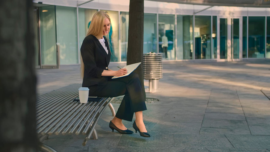 Woman writing in book while sitting on bench in city