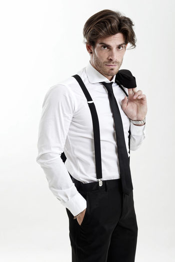 Portrait of man wearing suspenders standing with hands in pockets against white background