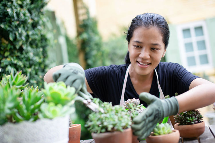 Portrait of a smiling young woman gardening in back yard