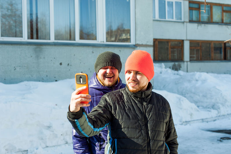 Man in warm clothing taking selfie with friend through mobile phone