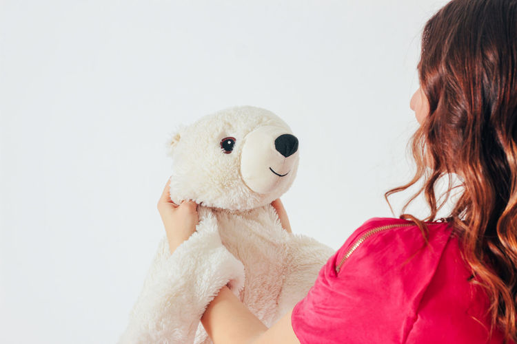 Portrait of woman with toy against white background