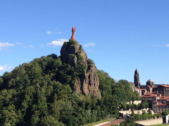 Our Lady of Le Puy Architecture Blue Building Exterior Built Structure Clear Sky Cloud Day Famous Place History Incidental People Low Angle View Mountain Our Lady Our Lady Of Le Puy Outdoors Rock - Object Rock Formation Sky Sunlight Travel Tree