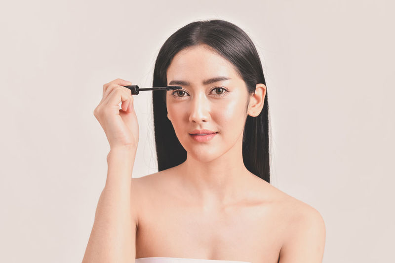Adult Beautiful Woman Beauty Body Part Females Front View Hairstyle Headshot Holding Human Body Part Human Face Indoors  Looking At Camera Make-up Make-up Brush One Person Portrait Preparation  Self Improvement Studio Shot Women Young Adult Young Women